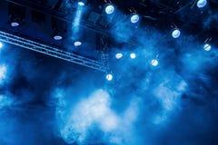 从聚光灯的蓝色光线通过在剧院或音乐厅的烟 表现或展示的照明设备 免版税库存照片