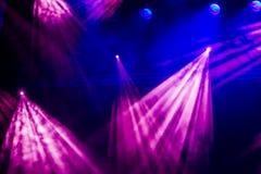 从聚光灯的蓝色和紫色光芒通过在剧院或音乐厅的烟 照明设备equipment.conference大厅泛光灯, 免版税库存图片