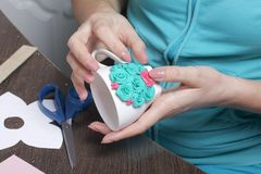 从聚合物黏土的工艺 妇女黏附一朵涂胶的聚合物黏土花到杯子 用灰泥装饰的杯子由聚合物黏土制成 库存图片