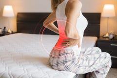 从背部疼痛的妇女痛苦由于难受的床垫 免版税库存照片
