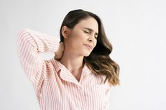 从脖子痛的年轻女人痛苦 免版税库存照片