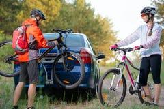 从自行车机架的年轻夫妇Unmounting登山车在汽车 冒险和家庭旅行概念 库存照片