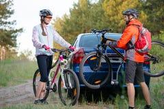 从自行车机架的年轻夫妇Unmounting登山车在汽车 冒险和家庭旅行概念 免版税库存照片
