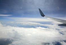 从舱窗的飞机空运神色 蓝天、白色下面云彩和土地 免版税库存照片