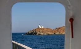 从船灯塔和贴水帕帕佐普洛斯教会的` s门的看法 Kea, Tzia海岛,希腊 1个背景覆盖多云天空 库存照片