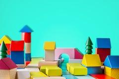 从色的块的玩具木房子在蓝色背景 大厦,建筑概念 房地产,修建从a的一个房子 免版税库存图片