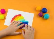从色的彩色塑泥的儿童模子 儿童` s手 库存照片