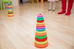 从色的木圆环的金字塔修造与在上面的一个小丑头 学会的婴孩和的小孩的玩具能快乐 图库摄影