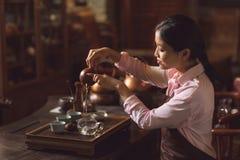 从茶壶的年轻主要倾吐的茶 免版税库存图片