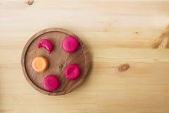 从莓和橙色巴黎人法国蛋白杏仁饼干的莓果绯红色桃红色蛋白杏仁饼干从在一块木地道板材的芒果 库存照片