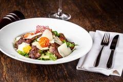 从莴苣、莴苣和冰山的混合的沙拉离开,与西红柿,橙色和烤牛肉在格栅 库存照片