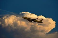 从获取高度的精神航空公司的飞机在起飞以后,在美丽的日落天空 库存图片