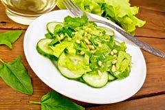 从菠菜和黄瓜的沙拉与在木板的叉子 免版税库存照片