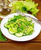 从菠菜和黄瓜的沙拉与在木桌上的叉子 库存照片