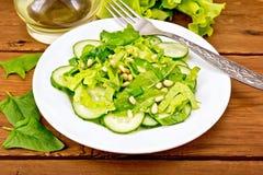 从菠菜和黄瓜的沙拉与在桌上的松子 免版税图库摄影