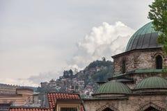 从萨拉热窝,波黑的市中心的清真寺,有萨拉热窝典型的背景有小屋的小山的 图库摄影