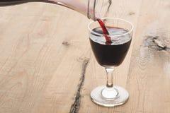 从蒸馏瓶倾吐的红葡萄酒 免版税库存图片