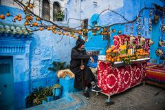 从蓝色城市的橙色卖主 库存图片