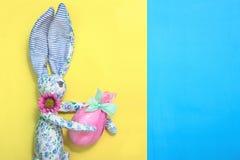 从蓝色织品的一只滑稽的复活节兔子在花在他的手上拿着一个复活节彩蛋 鸡蛋在礼物桃红色纸和绿色ri被包裹 免版税库存图片
