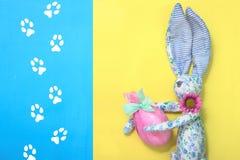 从蓝色织品的一只滑稽的复活节兔子在花在他的手上拿着一个复活节彩蛋 它在桃红色纸和绿色丝带被包裹 免版税库存照片