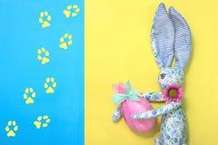从蓝色织品的一只滑稽的复活节兔子在花在礼物桃红色纸和绿色丝带在他的手上拿着一个复活节彩蛋被包裹 免版税库存照片