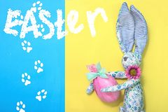 从蓝色织品的一只滑稽的复活节兔子在花在礼物桃红色纸,绿色丝带在他的手上拿着一个复活节彩蛋被包裹 Ye 库存照片