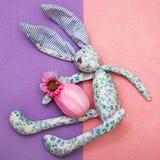 从蓝色,白色织品的创造性的滑稽的兔宝宝在他的手上拿着一个复活节彩蛋 鸡蛋在礼物与薄荷的绿色r的桃红色纸被包裹 库存照片