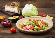 从蕃茄、鲕梨、玉米、红洋葱和莴苣叶子的开胃素食主义者沙拉 免版税库存照片