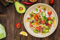 从蕃茄、鲕梨、玉米、红洋葱和莴苣叶子的开胃素食主义者沙拉 库存照片