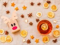 从被回收的纸的生态鹿工艺在与杯子的亚麻制背景热的茶、柠檬、桔子和装饰 免版税库存图片