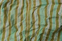 从被弄皱的衣裳片断的绿色棕色织品纹理  库存照片
