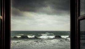 从被打开的窗口与大风雨如磐的波浪和剧烈的天空的剧烈的海视图在雨和风暴天气期间在秋季在海co 免版税库存照片