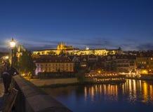从被阐明的圣Vitus大教堂哥特式churche和布拉格城堡全景查尔斯桥梁的夜视图与 库存照片