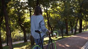 从走除一辆自行车以外的年轻女人的后面英尺长度在早晨公园或街道 走与的女孩 股票录像