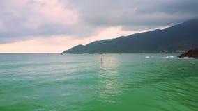 从起伏式波的飞行到paddleboard的孤立女孩在海洋 影视素材