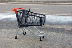 从超级市场的黑塑料空的推车在路的沥青的 库存图片