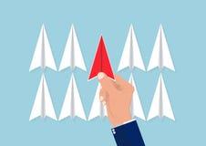 从转换型飞机的手采摘红色纸飞机,选择正确的目标和资源的计划的企业概念 库存图片