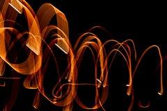 从轻的小条的明亮的螺旋样式在黑背景 库存照片