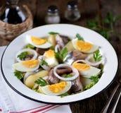 从轻盐味的鲱鱼、煮的土豆、鸡蛋和葱的沙拉与橄榄油和柠檬汁 土气样式 免版税库存照片