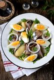 从轻盐味的鲱鱼、煮的土豆、鸡蛋和葱的沙拉与橄榄油和柠檬汁 土气样式 库存照片