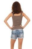 从返回的女孩在牛仔裤短裤 免版税库存照片