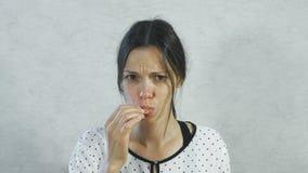 从酸的情感在女孩的面孔 畏缩深色的妇女吃酸蜜桔和 股票录像
