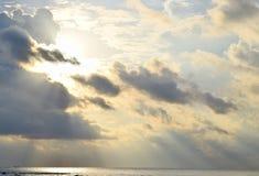 从金黄黄色太阳的明亮的光束在乌云和仍然延长神的祝福海水的下降后  免版税库存照片