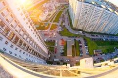 从阳台的高度的看法日落的和城市的庭院环境美化与汽车和停车处 免版税图库摄影