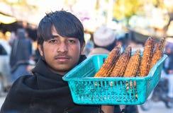 从阿富汗的一位年轻玉米卖主 库存照片