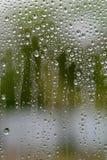 从雨的水下落在玻璃窗 图库摄影