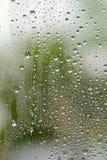 从雨的水下落在玻璃窗 免版税库存图片