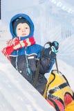 从雪幻灯片的愉快的男孩雪橇在五颜六色的管 免版税库存图片