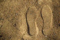 从鞋子的脚印在湿沙子 免版税库存照片