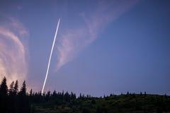 从飞机的一串白色足迹在晚上天空,在一个黑暗的森林水平的框架 库存图片